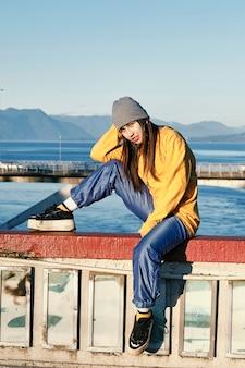 Ritratto di giovane donna hip-hop seduto su un ponte in uno spazio naturale.