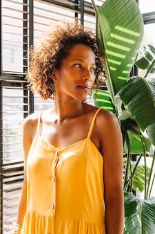 Ritratto di giovane donna in abito giallo in piedi vicino alla finestra