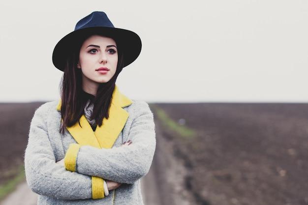 Ritratto di giovane donna in cappello e cappotto