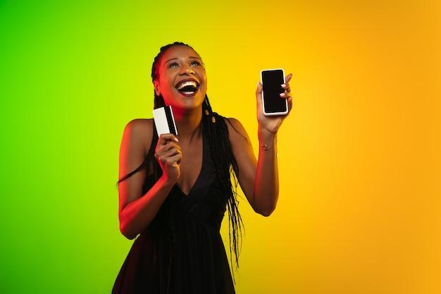 Ritratto di giovane donna in luce al neon su sfondo sfumato. ridendo e tenendo in mano un telefono e una carta di credito.