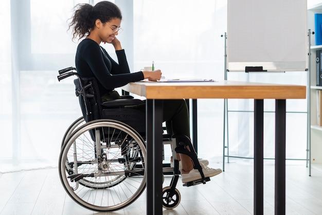 Ritratto di giovane donna in sedia a rotelle in ufficio