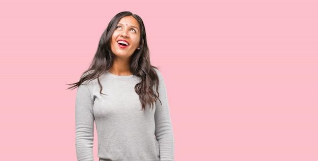 Ritratto di giovane donna indiana alzando lo sguardo, pensando a qualcosa di divertente e avendo un'idea, concetto di immaginazione, felice ed emozionato