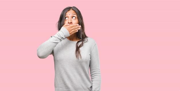 Ritratto di giovane donna indiana che copre la bocca, simbolo di silenzio e repressione, cercando di non dire nulla