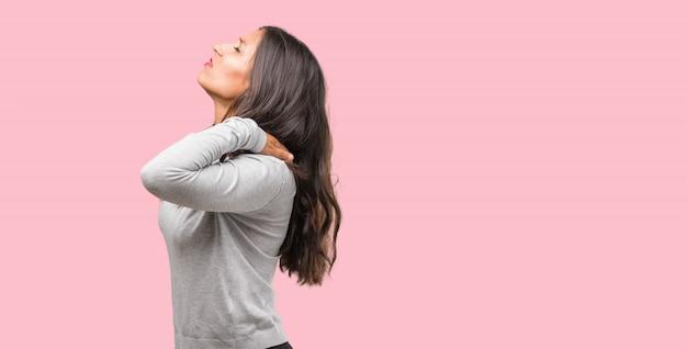 Ritratto di giovane donna indiana con dolore alla schiena a causa di stress da lavoro, stanco e astuto