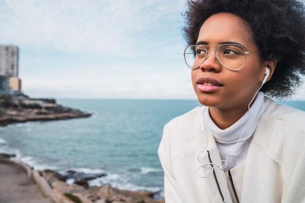 Ritratto di giovane donna latina che ascolta la musica con gli auricolari con il mare sullo spazio. musica, stile di vita.