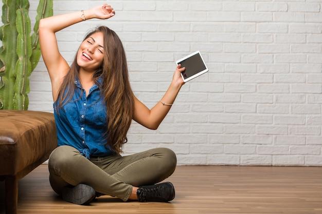 Ritratto di giovane donna latina che si siede sul pavimento che ascolta la musica, ballante e divertendosi, muovendosi, gridando ed esprimendo felicità, concetto di libertà. in possesso di un tablet.