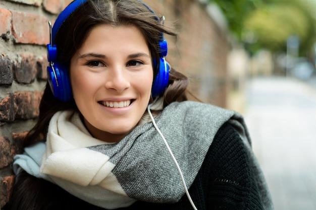 Ritratto di giovane donna latina con le cuffie blu