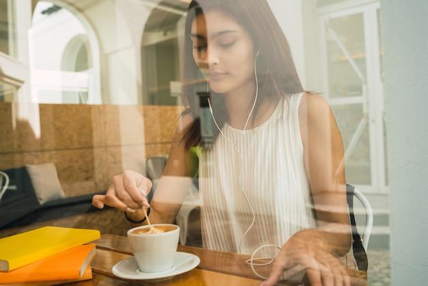 Ritratto di giovane donna latina godendo e bevendo una tazza di caffè al bar