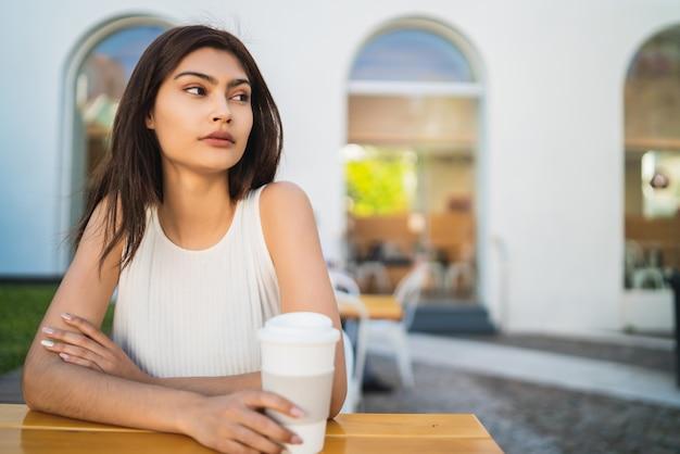 Ritratto di giovane donna latina godendo e bevendo una tazza di caffè all'aperto presso la caffetteria