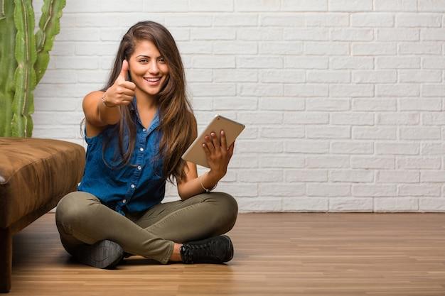 Ritratto di giovane donna latina seduta sul pavimento allegro ed emozionato