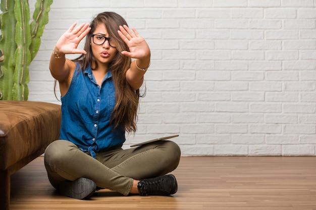 Ritratto di giovane donna latina seduta sul pavimento serio e determinato, fermare il gesto