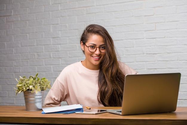 Ritratto di giovane donna latina studente seduto sulla sua scrivania con le mani sui fianchi, in piedi