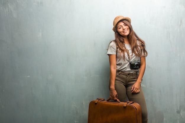 Ritratto di giovane donna latina viaggiatore contro un muro allegro e con un grande sorriso