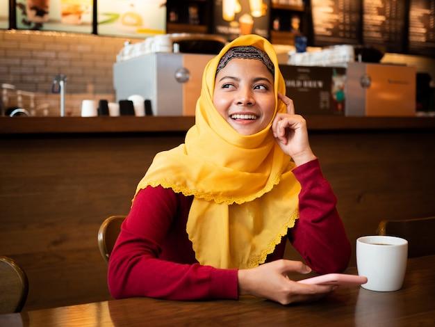 Ritratto di giovane donna musulmana in caffetteria