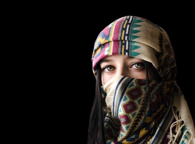 Ritratto di giovane donna orientale in paranja isolato su sfondo nero