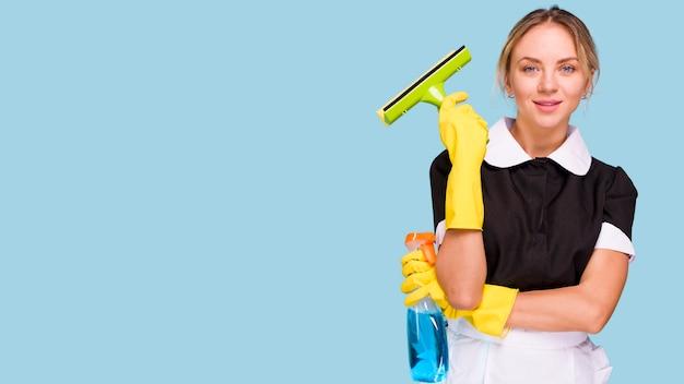 Ritratto di giovane donna più pulita tenendo tergicristallo di plastica e bottiglia di detersivo guardando la fotocamera