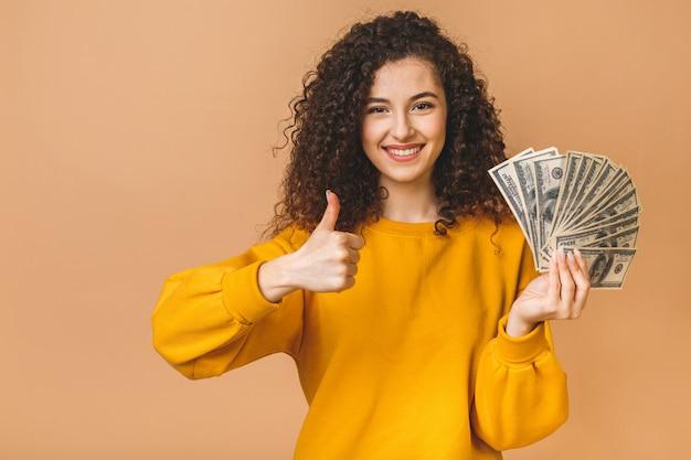 Ritratto di giovane donna riccia allegra che tiene le banconote e che celebra dei soldi isolate sopra fondo beige. pollice su.