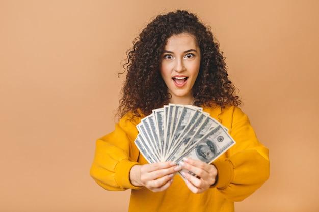Ritratto di giovane donna riccia allegra che tiene le banconote e che celebra dei soldi isolate sopra fondo beige.