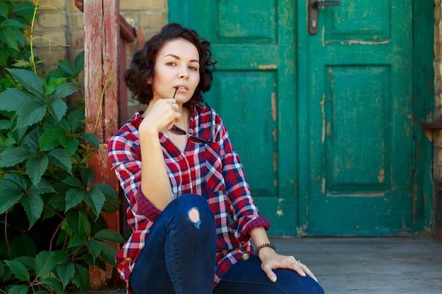 Ritratto di giovane donna riccia vicino alla vecchia parete della casa. ragazza sorridente ed emozionale in jeans e camicia rossa e occhiali da sole sulla strada della città. giovane donna sveglia all'aperto nel giorno soleggiato