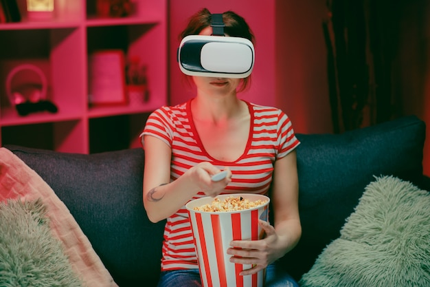Ritratto di giovane donna seduta sul divano e con l'auricolare vr, guardando qualcosa mentre si mangia popcorn e sorridente