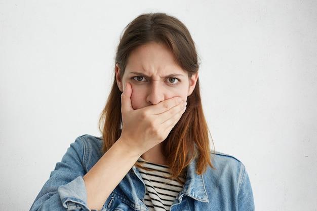 Ritratto di giovane donna seria in giacca di jeans che copre la bocca con la mano mentre nasconde il segreto