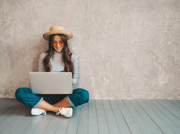 Ritratto di giovane donna sorridente creativa in occhiali da sole. bella ragazza che si siede sul pavimento vicino alla parete grigia.