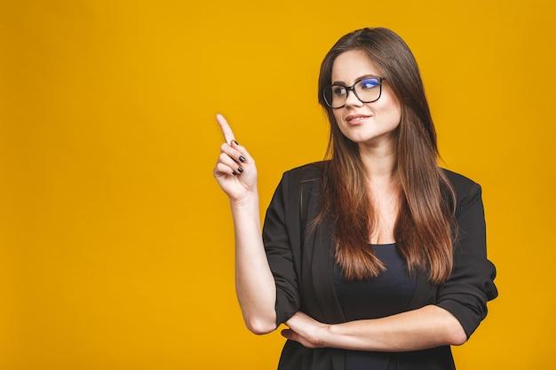 Ritratto di giovane donna sorridente di affari che indica su e che guarda