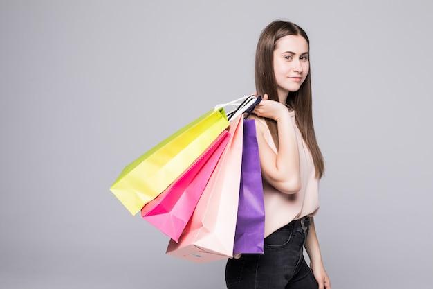 Ritratto di giovane donna sorridente felice con i sacchetti della spesa sopra la parete bianca