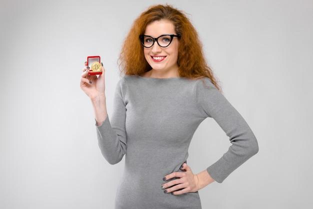 Ritratto di giovane donna sorridente felice della bella testarossa in vestiti grigi in vetri che mostrano bitcoin come concetto di criptovaluta su fondo grigio