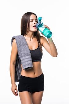 Ritratto di giovane donna sorridente felice nell'usura di forma fisica con la bottiglia di acqua, isolato su bianco