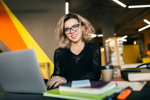 Ritratto di giovane donna sorridente graziosa che si siede al tavolo in camicia nera che lavora al computer portatile in ufficio di co-working, con gli occhiali
