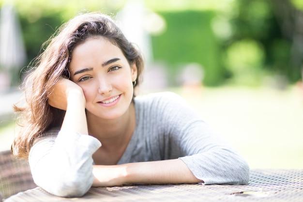 Ritratto di giovane donna sorridente seduta al tavolo