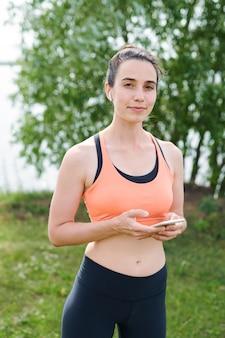 Ritratto di giovane donna sportiva contenuto in abbigliamento sportivo in piedi nel parco e utilizzando gadget moderni