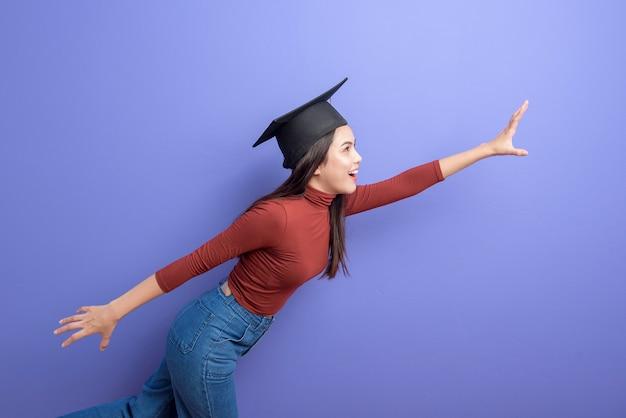 Ritratto di giovane donna studente universitario con cappello di laurea su sfondo viola