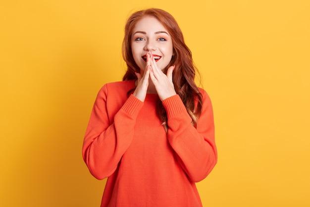 Ritratto di giovane donna stupita in posa con l'espressione facciale eccitata isolata, tenendo le mani sulla bocca