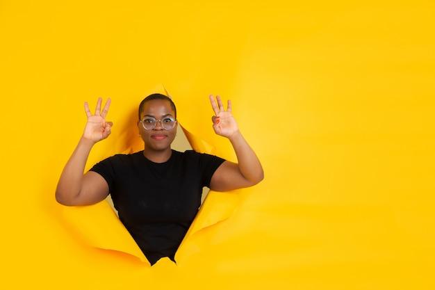 Ritratto di giovane donna su sfondo sfondato strappato giallo