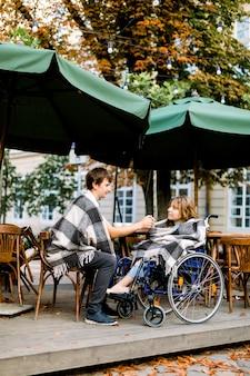 Ritratto di giovane donna su una sedia a rotelle che si diverte durante un appuntamento con il suo bell'uomo