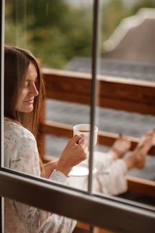 Ritratto di giovane donna sul balcone che tiene una tazza di caffè o un tè al mattino. lei in camera d'albergo guardando la natura in estate. la ragazza è vestita con indumenti da notte eleganti. tempo di relax