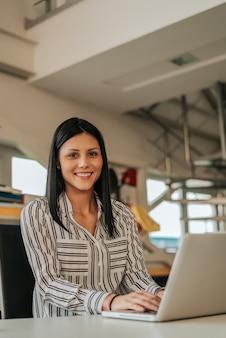 Ritratto di giovane donna sul posto di lavoro con computer portatile.