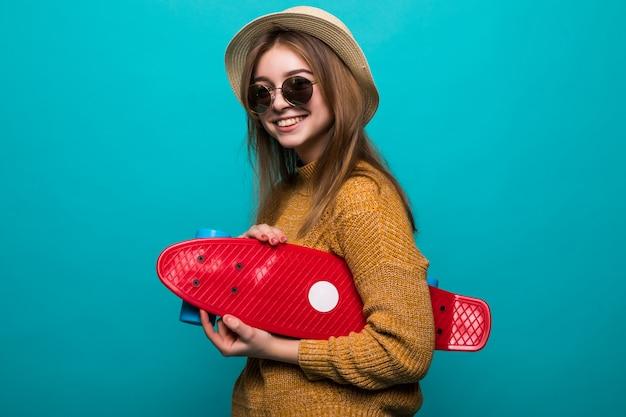 Ritratto di giovane donna teenager in occhiali da sole e cappello tenendo lo skateboard mentre in piedi isolato su muro verde
