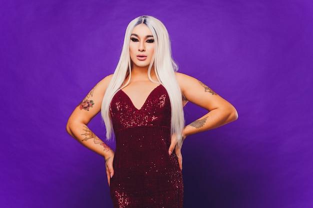 Ritratto di giovane donna transgender in abito rosso con paillettes