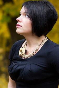 Ritratto di giovane e bella donna bruna in autunno parco. la bellezza della natura.