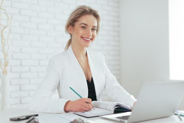 Ritratto di giovane e bella donna che lavora in ufficio.