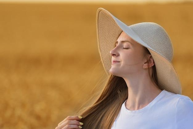 Ritratto di giovane e bella donna con cappello su sfondo neutro caldo.