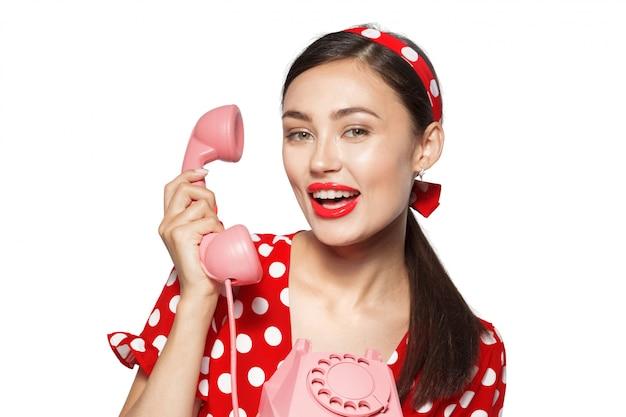 Ritratto di giovane e bella donna con telefono, vestito in stile pin-up.