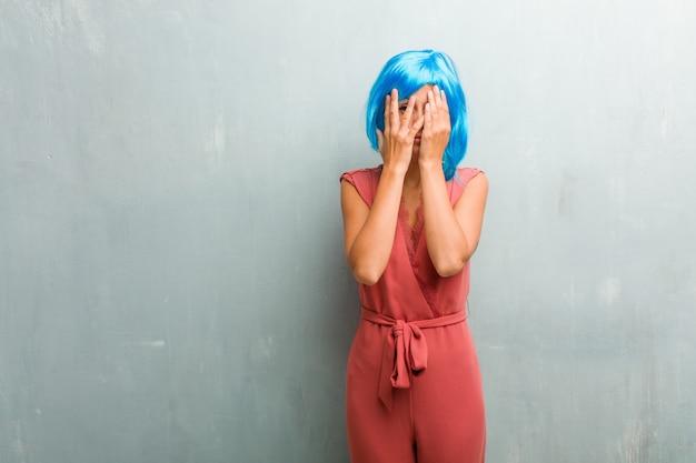 Ritratto di giovane elegante donna bionda si sente preoccupato e spaventato, guardando e coprendo il viso, il concetto di paura e ansia. indossa una parrucca blu.