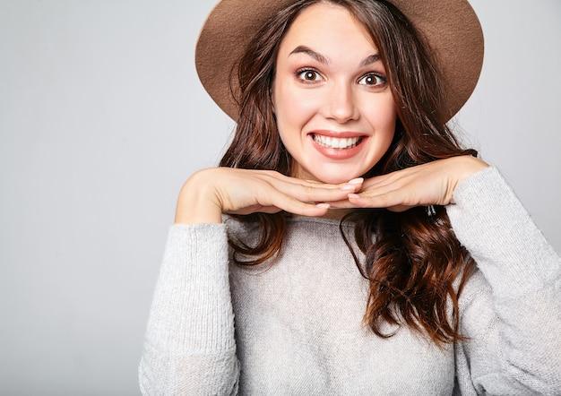 Ritratto di giovane elegante modello ridendo in abiti estivi casual grigi in cappello marrone con trucco naturale