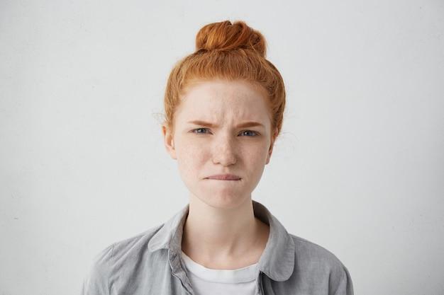 Ritratto di giovane femmina europea di zenzero infelice con le lentiggini su tutto il viso alla ricerca, con occhi doloranti, mordendosi il labbro inferiore come se cercasse di alleviare il dolore. emozioni e sentimenti umani