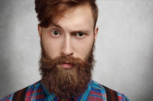 Ritratto di giovane hipster europeo con la pelle lentigginosa e la barba sfocata allo zenzero che aggrotta le sopracciglia, con un'espressione infelice o arrabbiata sul viso, scontento di qualcosa.