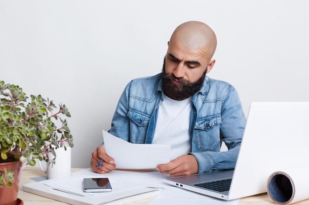 Ritratto di giovane imprenditore serio con folta barba nera seduto in ufficio accogliente, lavorando su un piano aziendale potenziale utilizzando il computer portatile